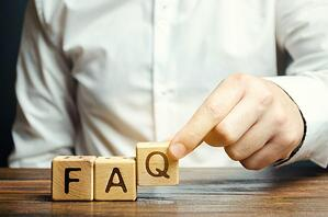 Businessman puts wooden blocks with the word FAQ