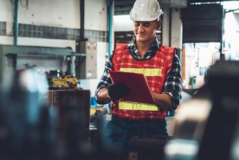 Manufacturing worker working with clipboard to do job procedure checklist